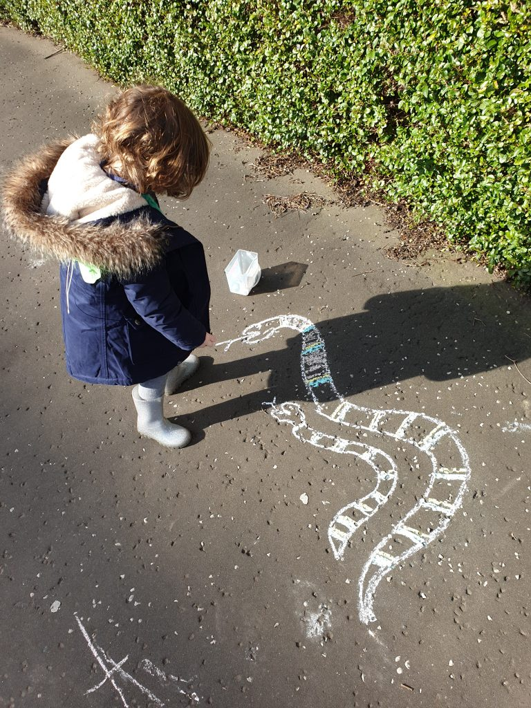 The image shows a 3 year old girl in a blue coat chalking on the pavement. Two chalk snakes have been drawn.