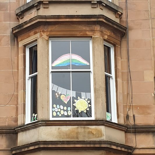 The image shows a series of drawings and paper cut outs hanging in the bay window of a sandstone tenement flat: a sun, easter eggs, a heart and a rainbow.