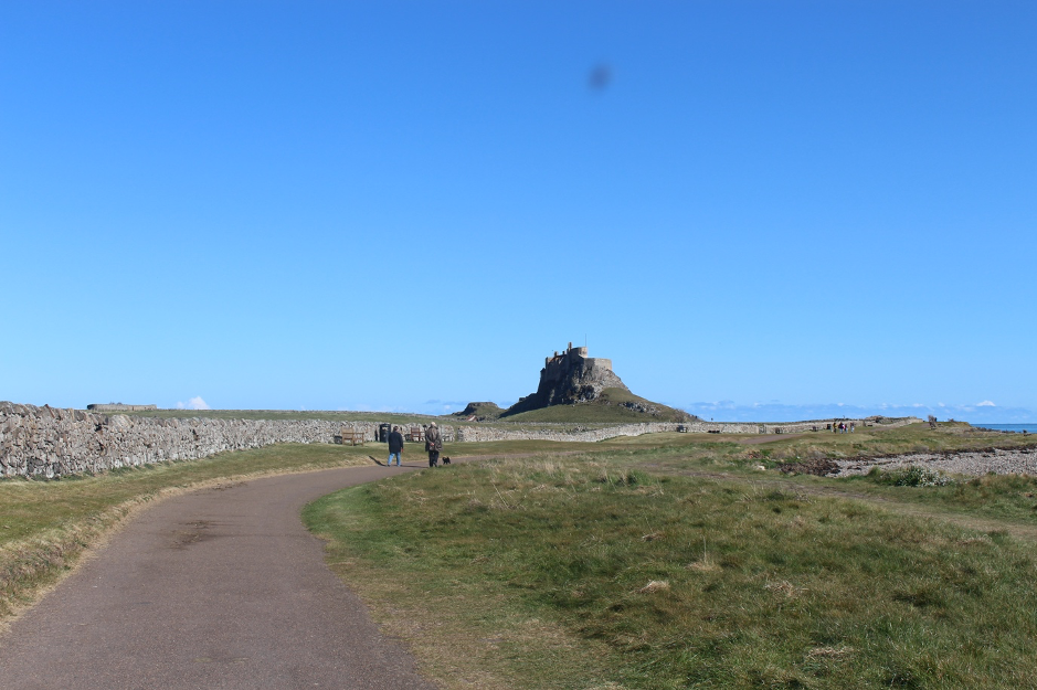 a path with two people on it leads to a castle in the distance