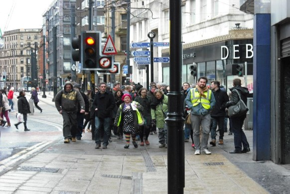 a crowd of people walk down a city street