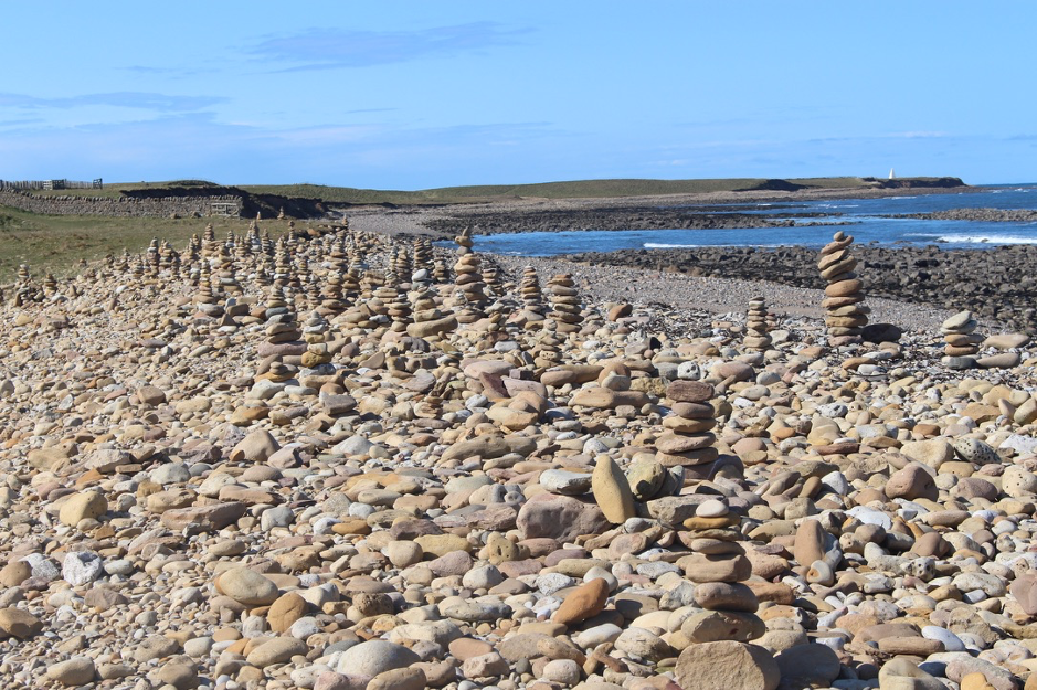 rocks and pebbles, some stacked, along a shoreline