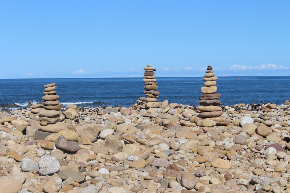 three towers of stacked rocks against the backdrop of the sea