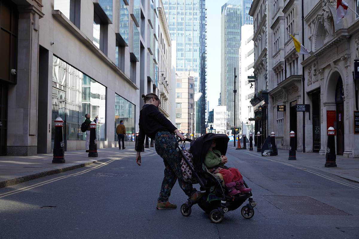A woman with a pram, standing in the middle of an empty road, with tall glass, concrete and stone buildings all around.