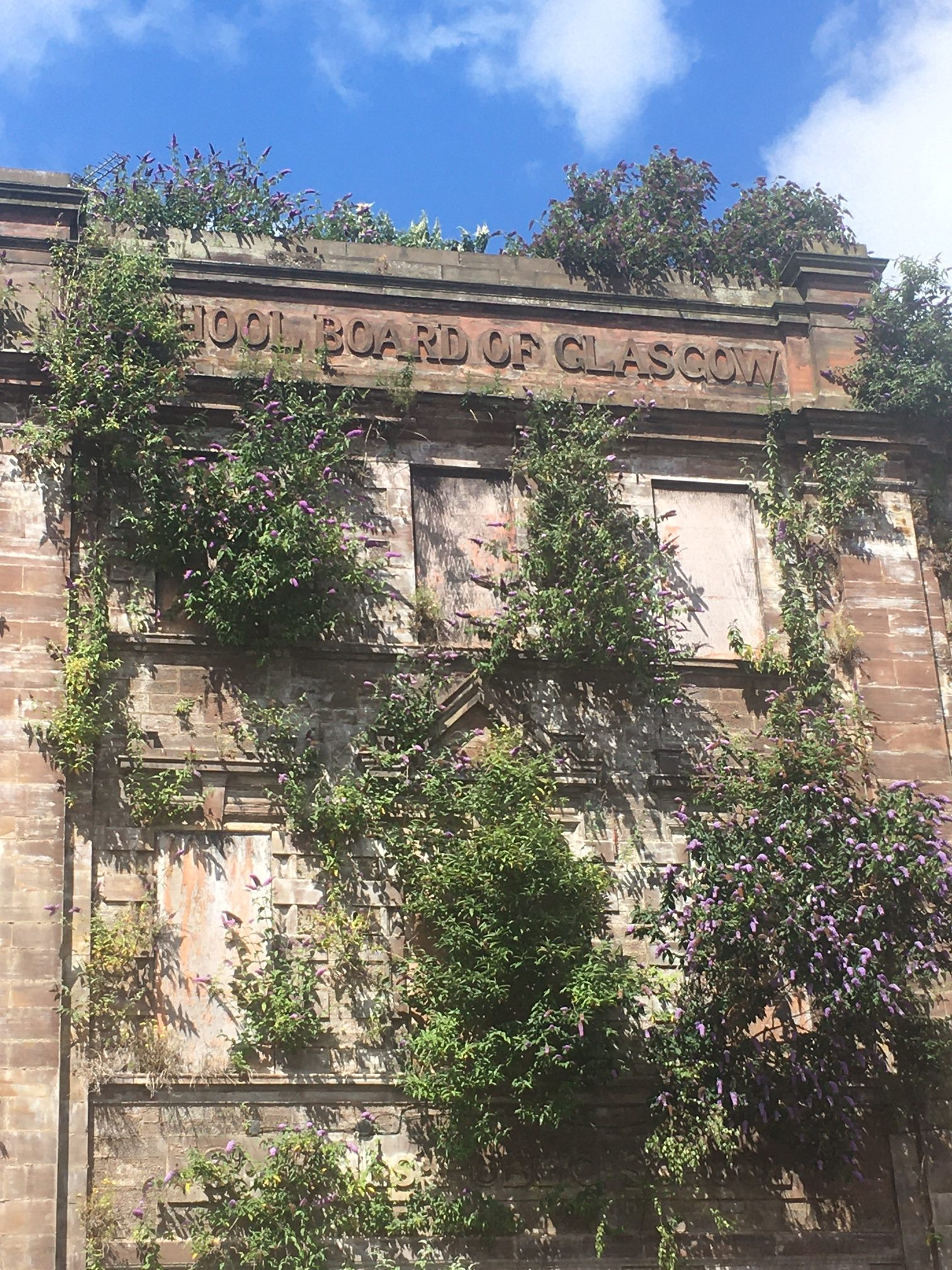 The photograph shows St James' school, with buddleia sprouting profusely over the front elevation.