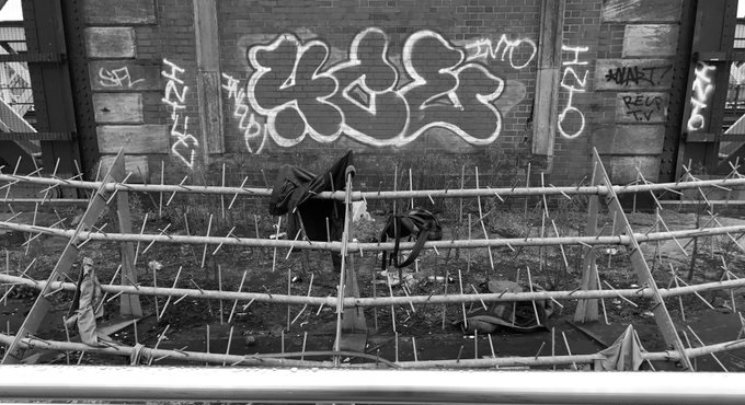 The black and white image shows grafitti on the brick base of Hungerford Bridge in London. There are barbed spikes in the foreground with clothing tangled up in them.