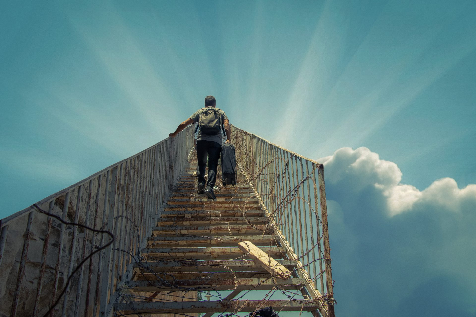 A man ascends a stairway to the sky carrying a suitcase. The stairs are mired with barbed wire.
