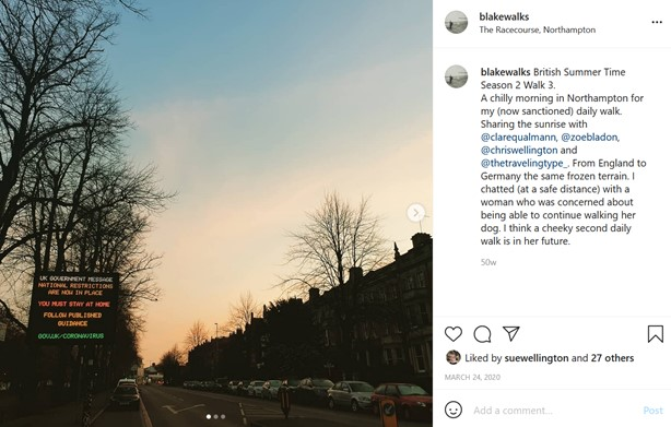 An Instagram post of a sunrise over a street with a row of Victorian houses on the right. On the left side of the image is a pavement running alongside the Racecourse Park. A large screen reads UK Government Message National Restrictions Are Now In Place You Must Stay At Home Follow Published Guidance Gov.uk/Coronavirus. On the other side of the post it reads: Blakewalks British Summer Time Season 2, Walk 3. A chilly morning in Northampton for my (now sanctioned) daily walk. Sharing the sunrise with @clarequalmann, @zoebladon, @chriswellington and @thetravelingtype_. From England to Germany on the same frozen terrain. I chatted (at a safe distance) with a woman who was concerned about being able to continue walking her dog. I think a cheeky second daily walk is in her future.