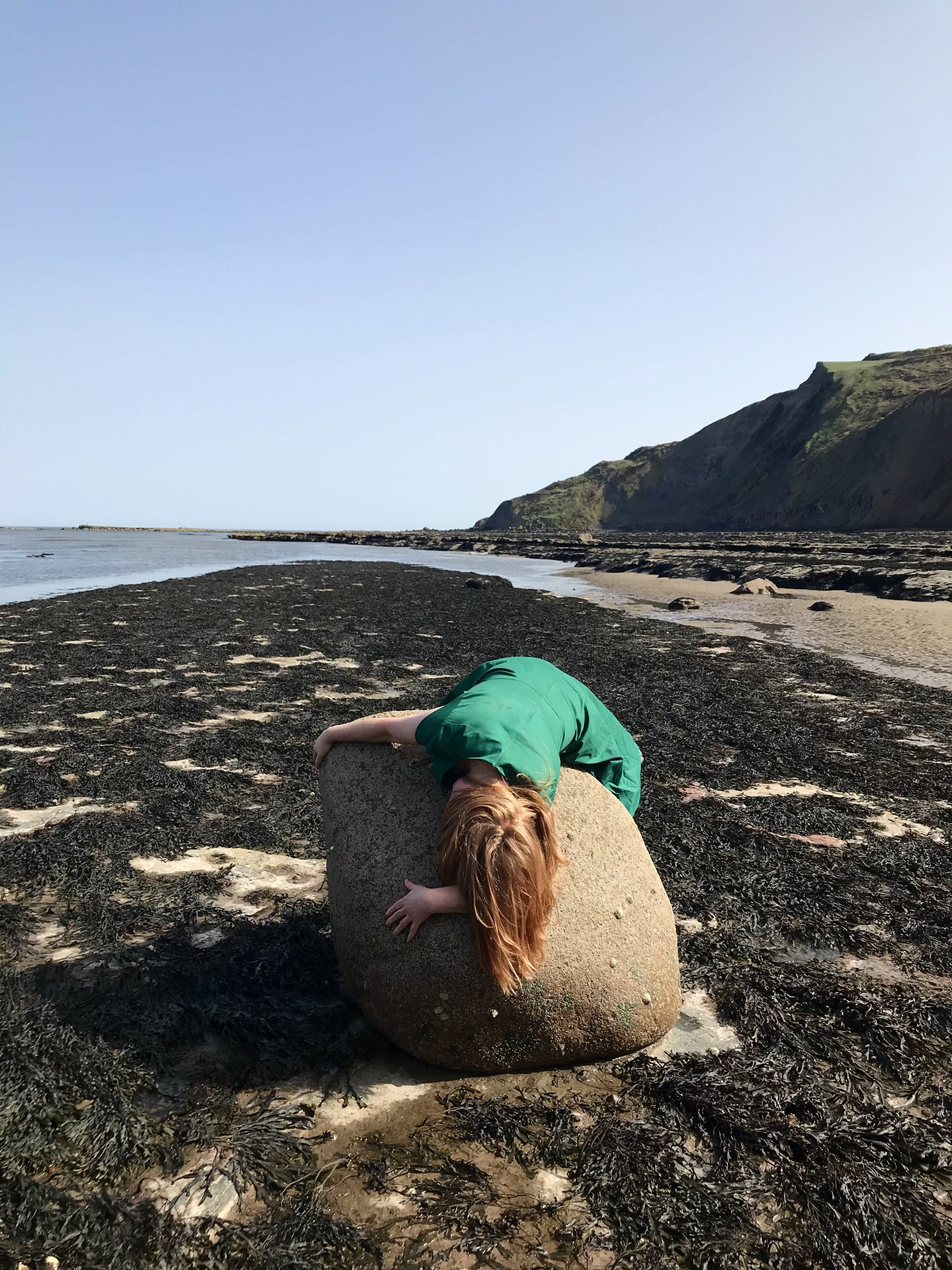 Ravenscar at low tide reveals an extraordinary number of fossils, rocks and scaurs that tell stories about costal erosion. This image captures Claire performing an action with a boulder, Norwegian in Origin, which has been deposited here from the last ice age.