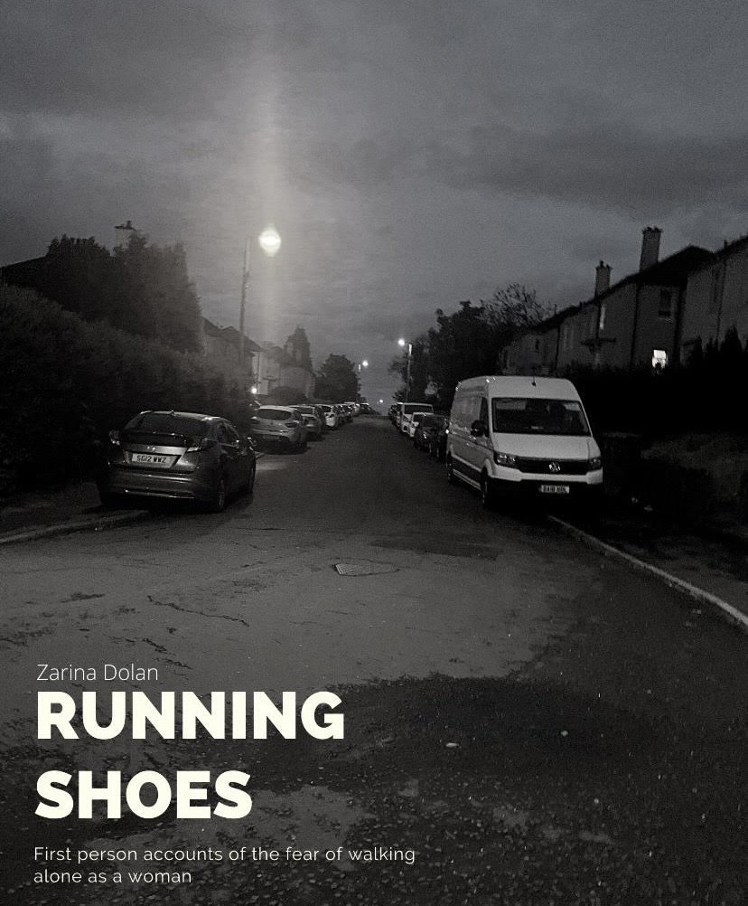 """The image is of a street lined with cars, it is the street the creator of Running Shoes commonly felt unsafe walking down on her way home from work. The image is in black and white and has white writing at the bottom that reads """"Running Shoes: first person accounts of the fear of walking alone as a woman"""""""