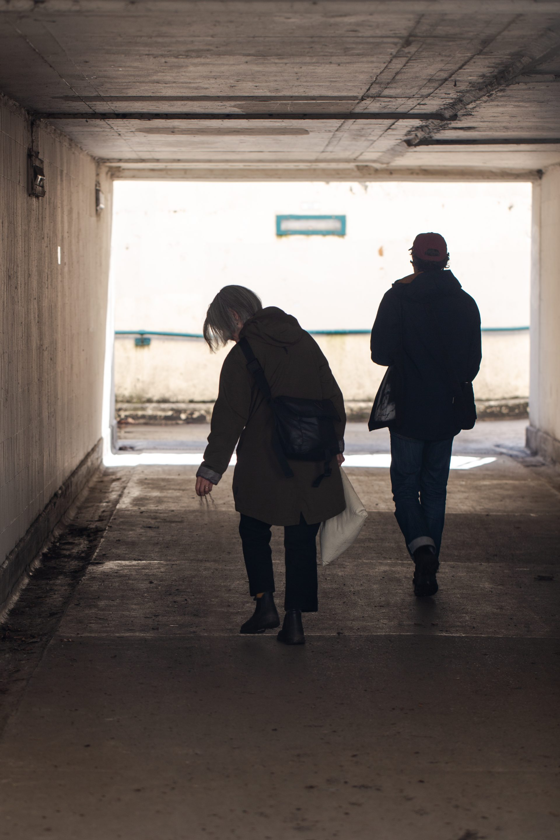 Two people (the artists) walking through a road tunnel, sprinkling silt on the ground.