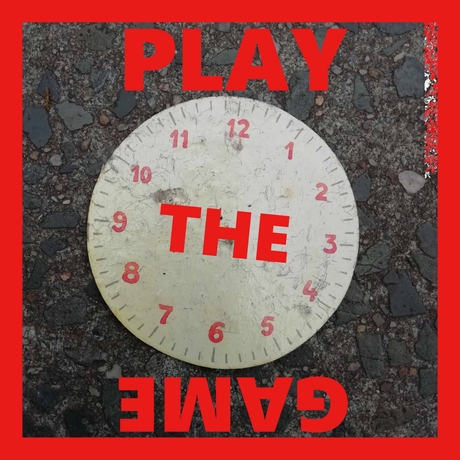 a photograph of a paper clock without hands on an asphalt pavement. The text reads 'Play the game' in bright red capitals.