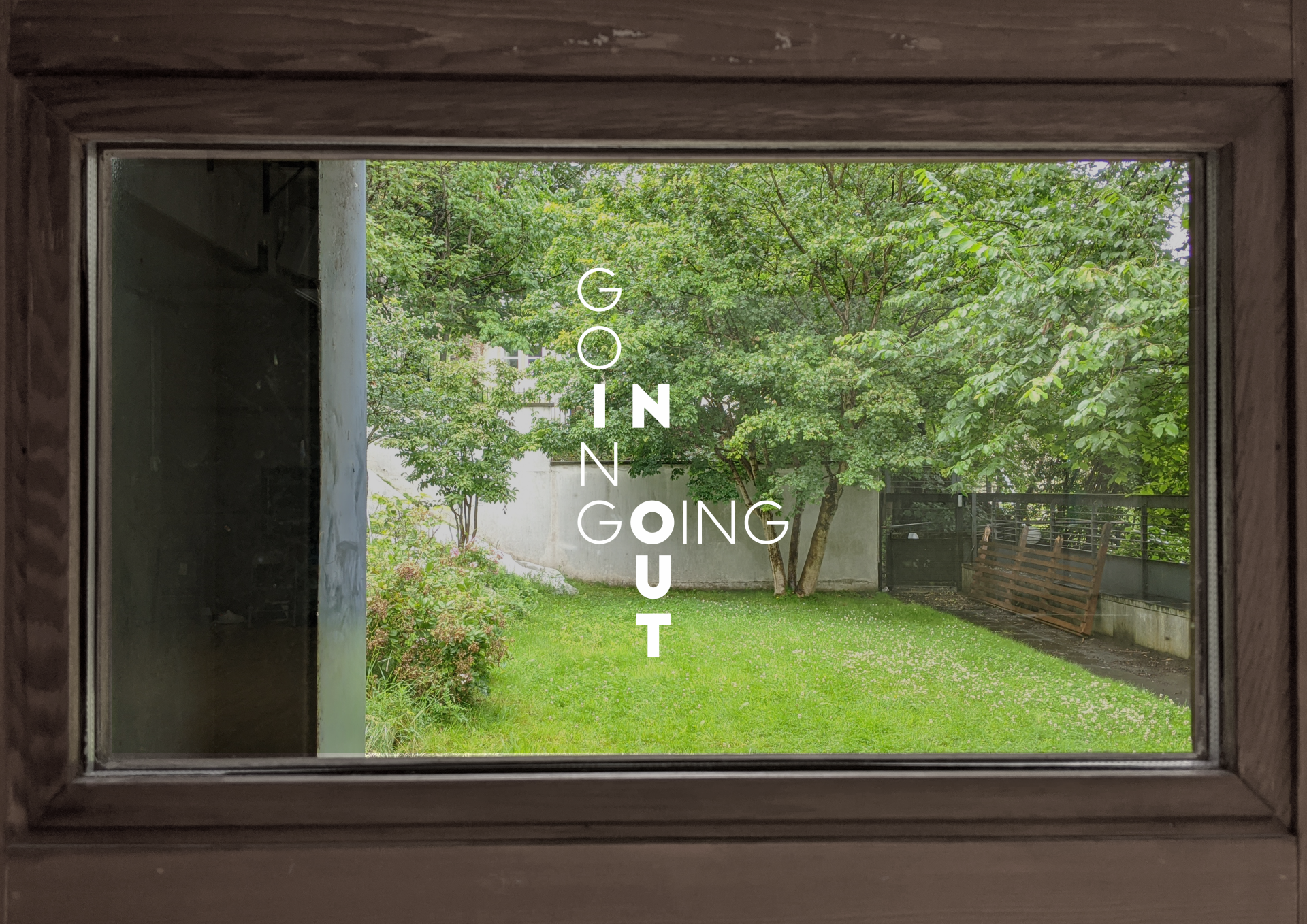 The viewer is indoors, looking out through a window, towards a lush, green garden. The words GOING IN GOING OUT are layered over the image in white, and intersect like answers in a crossword.