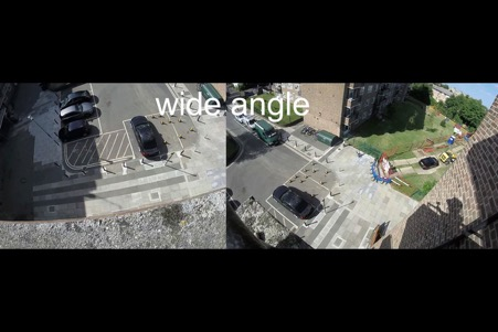 Two views, side by side, looking down on the courtyard of a housing estate. In the right view one can see the shadow of the person taking the video.