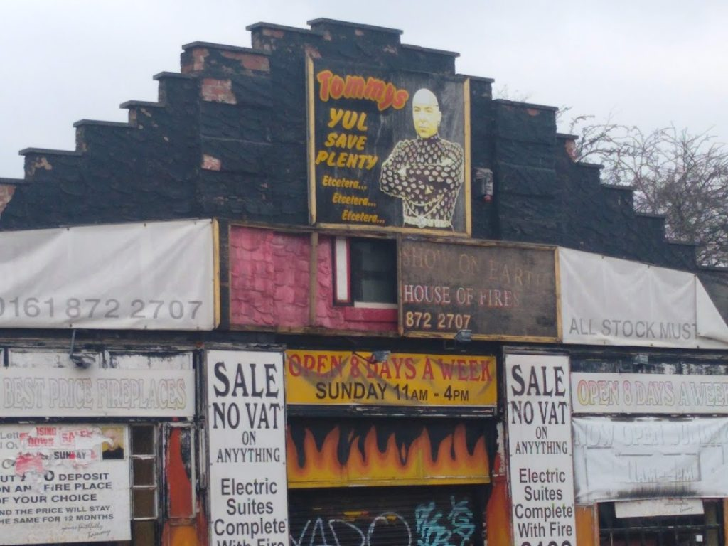 """A fireplace shop with lots of banners advertising sales and opening times. At the top of the gable the poster has a picture of Yul Bryner and the caption """"yul save plenty etcetera etcetera etcetera"""""""