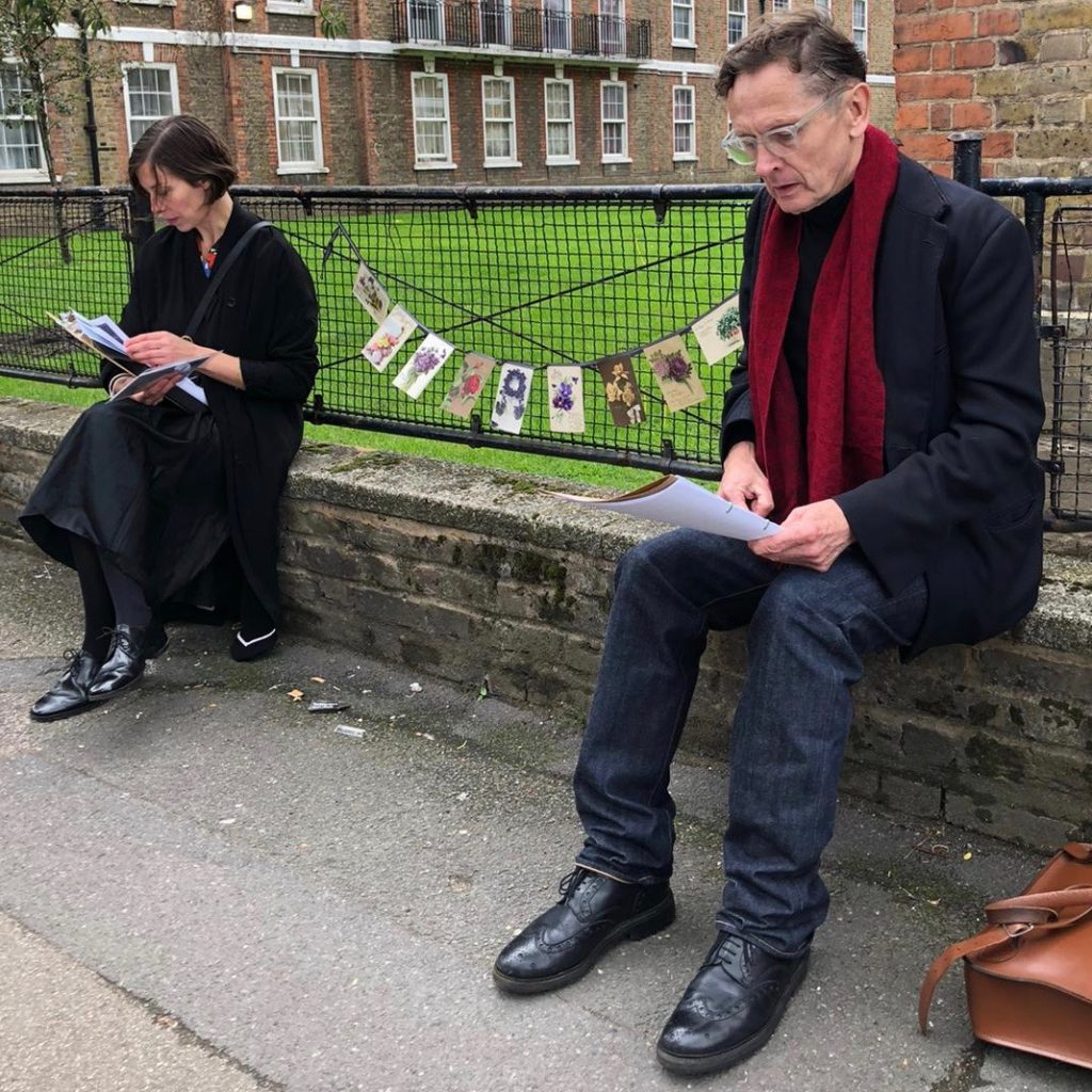 Two people (Corinne and Simon) sitting on a low wall. Between them is a string of antique postcards (displayed on the fence behind) picturing flowers.