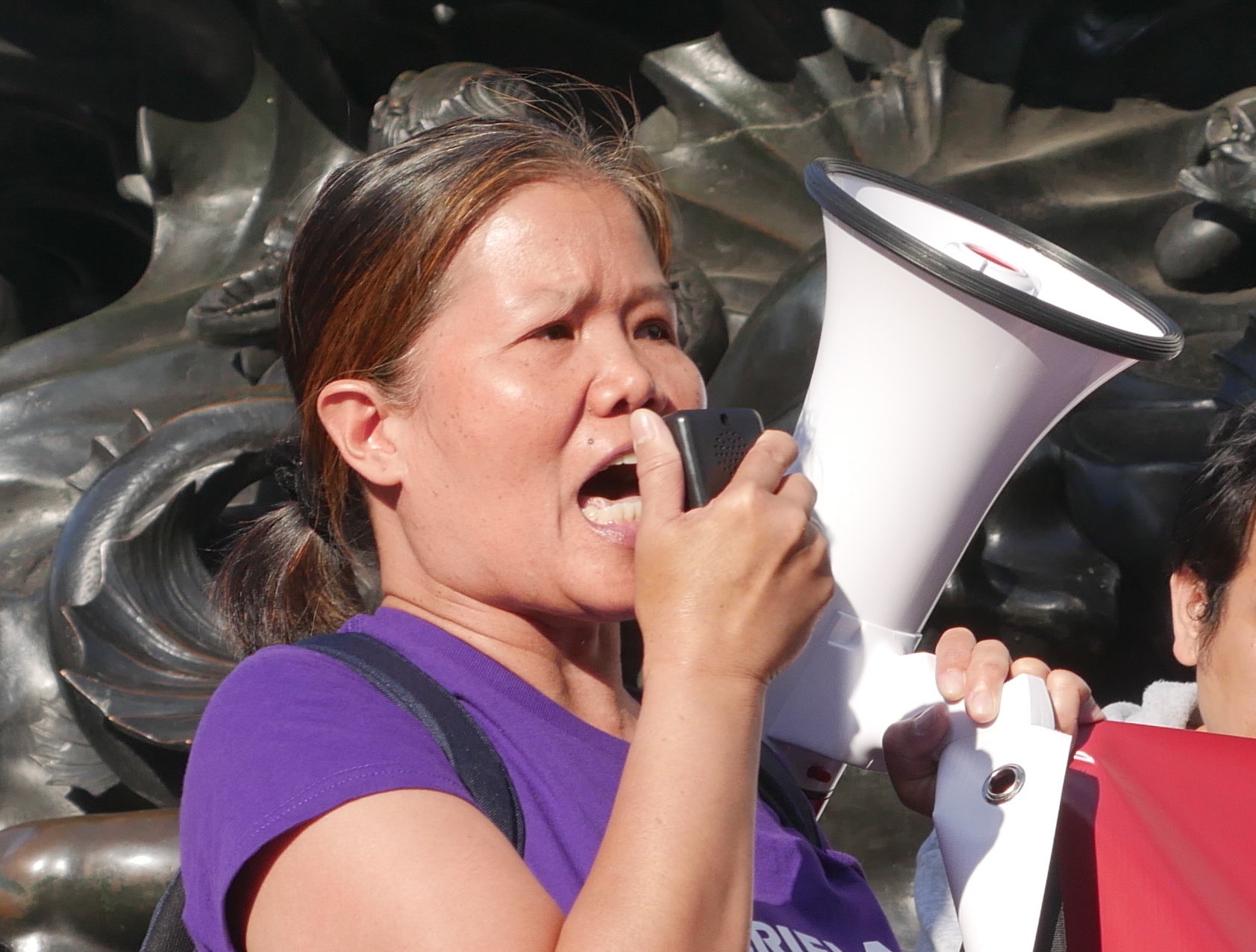 A Filipina migrant domestic worker is shouting passionately into a megaphone at a protest