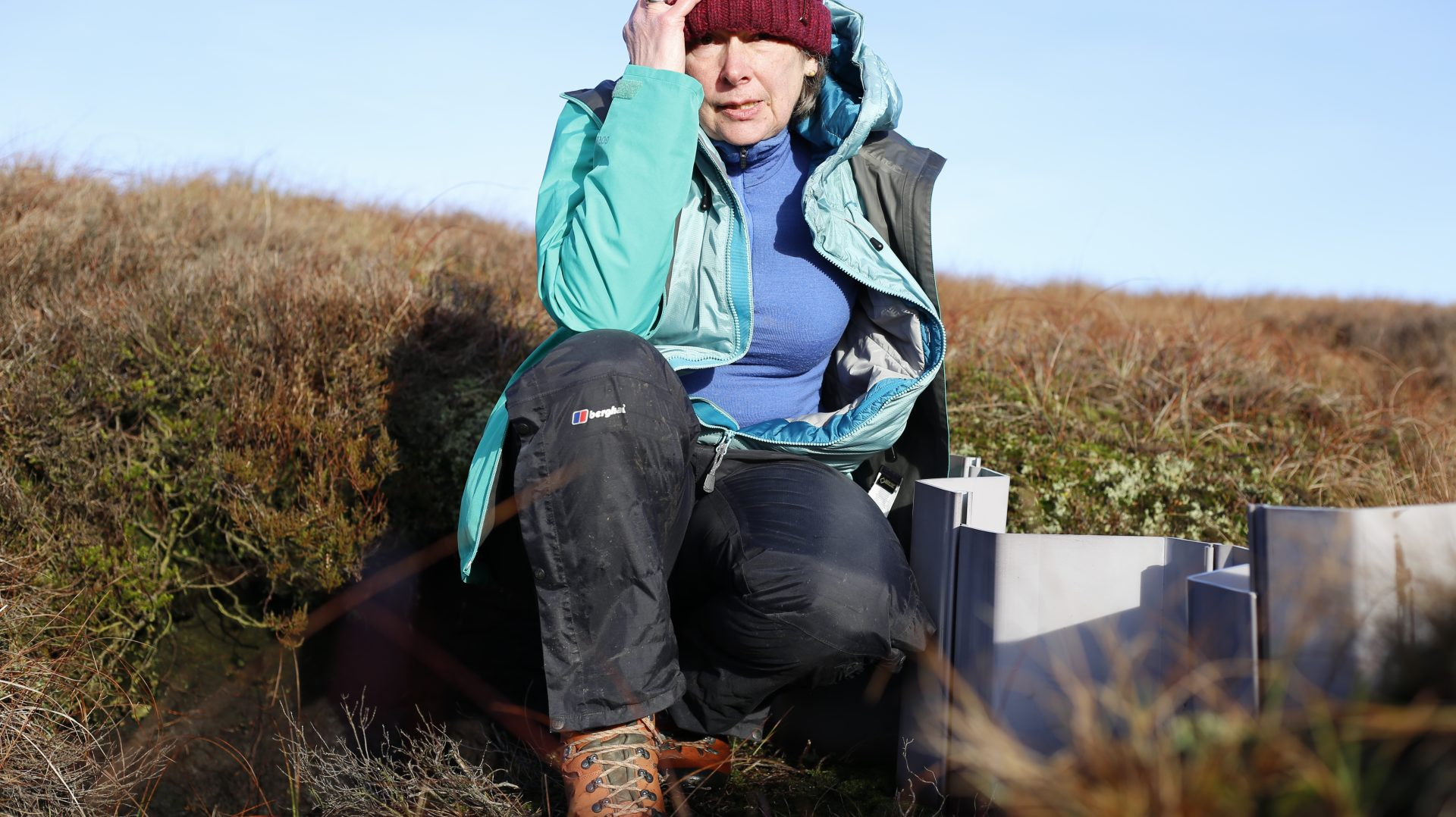 A female figure sits in the middle of the image next to a grey plastic peat gully dam. She is wearing orange walking boots, black trousers, a sky blue top, a turquoise jacket and a red woolly hat. She is surrounded by brown, green and orange vegetation. The sky is blue in the distant horizon.