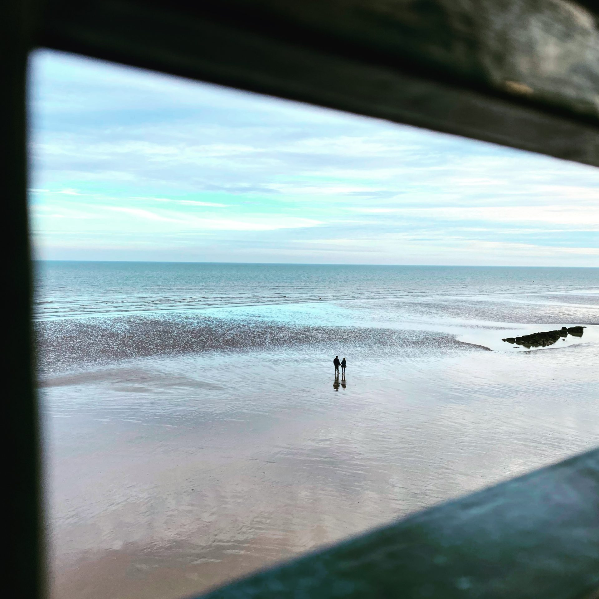 The image depicts two silhouetted figure walking along a beach at low tide. The image is framed through what looks like a window or mirror.