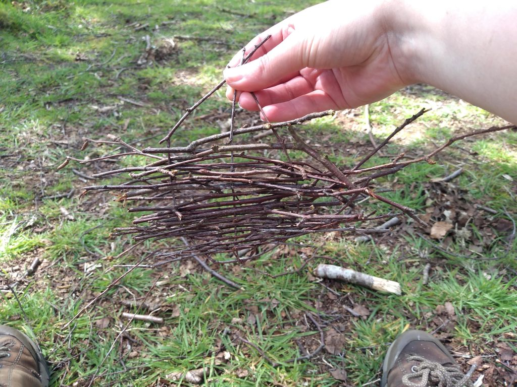 Small, hanging item made from birch twigs woven together.
