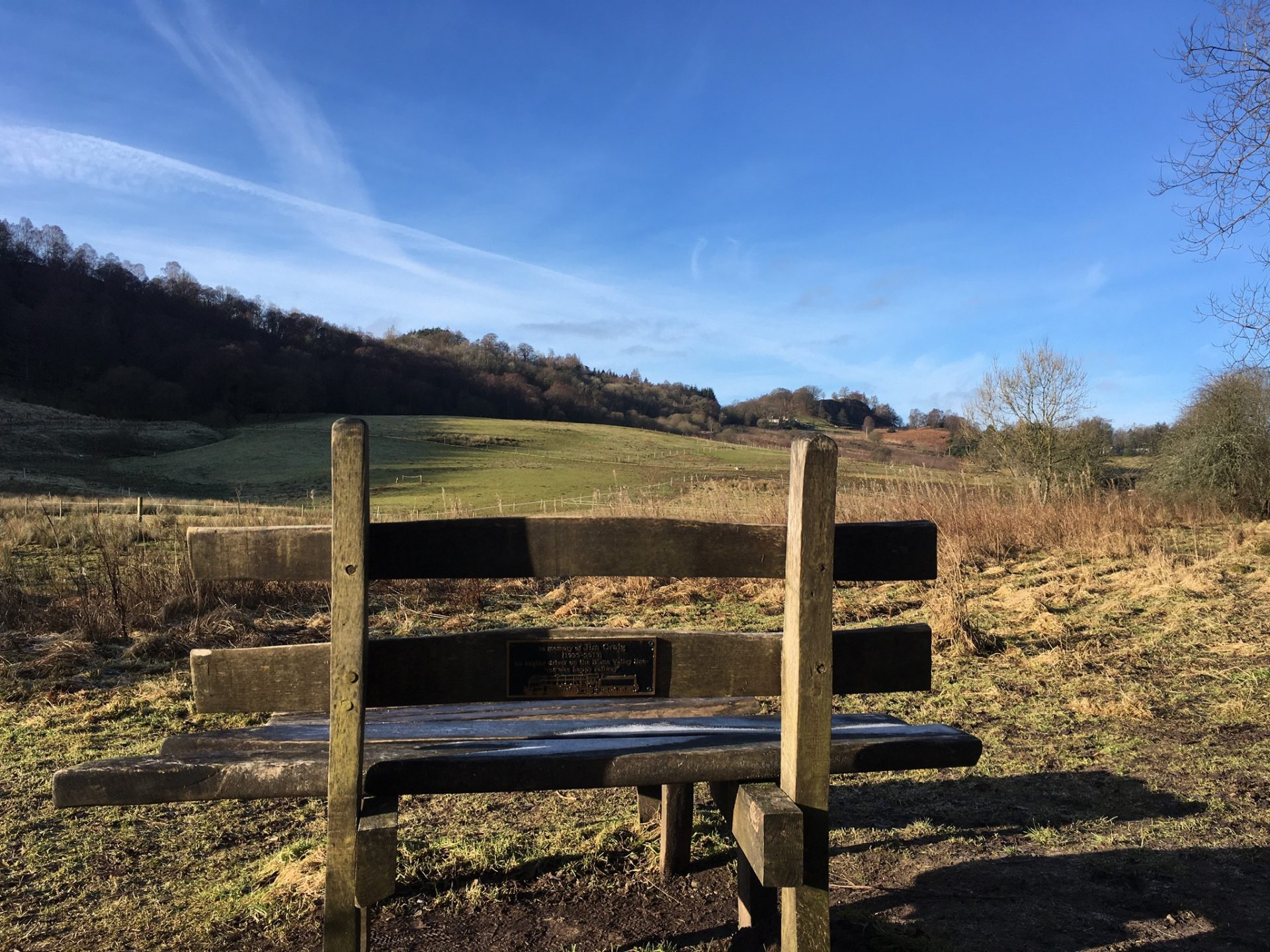 A handmade bench along the railway track in Blanefield, with a view towards Carbeth