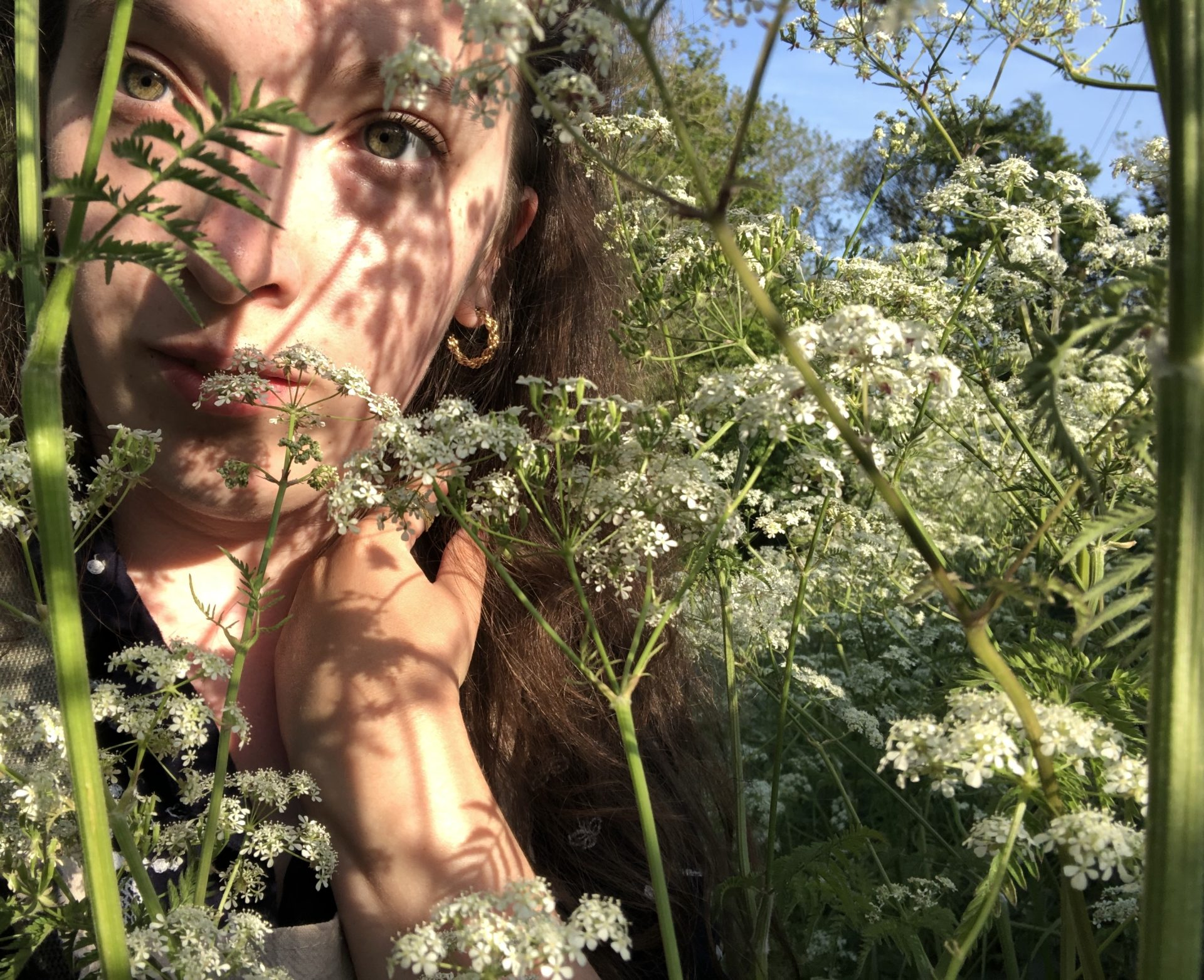 A self portrait of a woman leaning against a cow parsley plant the shadow of the plant hangs across her face.